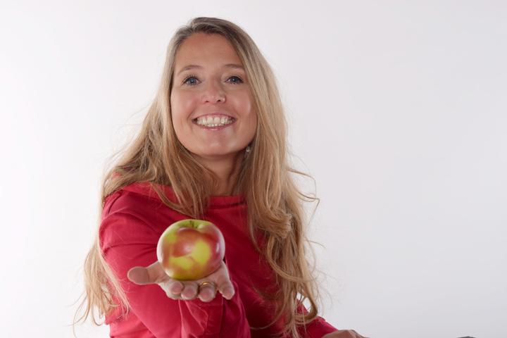 Frau reicht einen Apfel