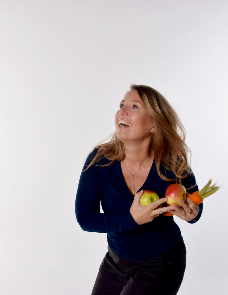 Frau beim Jonglieren von Obst und Gemüse